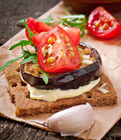 Vegetarian Diet Crispbread sandwiches with garlic cream cheese, roasted eggplant, arugula and cherry tomatoes on old wooden background photo