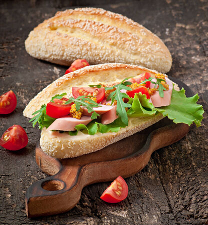Sandwich with sausage, lettuce, tomato and arugula on the old wooden background photo