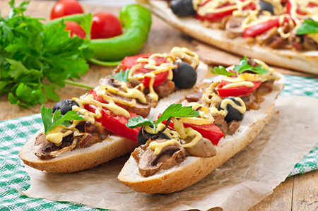 Baguette stuffed with veal and mushrooms with tomatoes and cheese photo