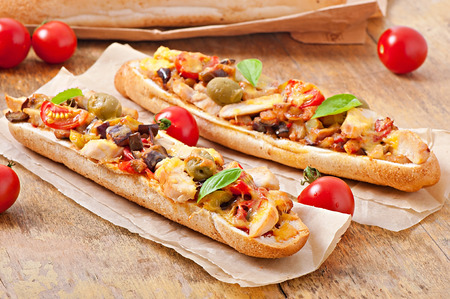 Big sandwich with roasted vegetables  zucchini, eggplant, tomatoes  and chicken with cheese and basil on old wooden background photo