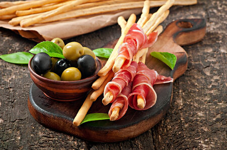 Grissini bread sticks with ham, olives, basil on old wooden background photo