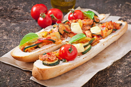 Big sandwich with roasted vegetables  zucchini, paprika , tomatoes  with cheese and basil on old wooden background photo