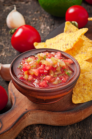 nacho chip: Mexican nacho chips and salsa dip in bowl on wooden background