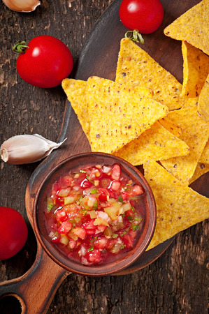 crunchy: Mexican nacho chips and salsa dip in bowl on wooden background