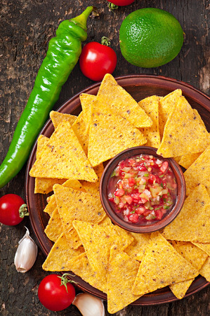 Mexican nacho chips and salsa dip in bowl on wooden background photo