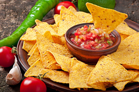 chips: Mexican nacho chips and salsa dip in bowl on wooden background
