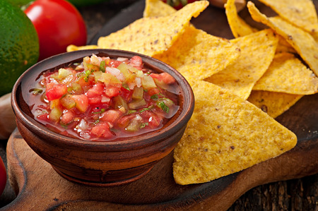 chips and salsa: Mexican nacho chips and salsa dip in bowl on wooden background