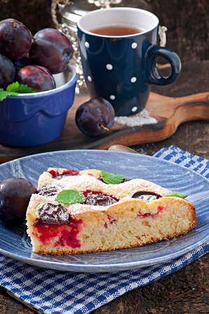 Delicious homemade cake with plums on a wooden background photo
