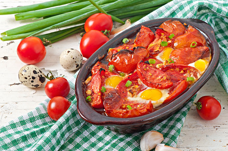 Baked tomatoes with garlic and eggs decorated with green onions photo