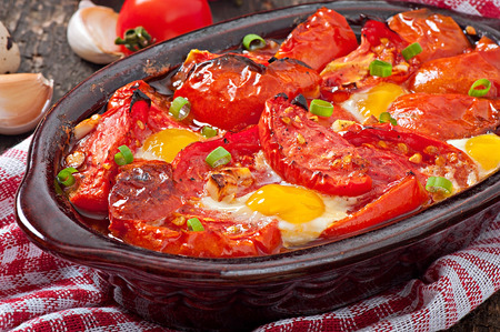 meatless: Baked tomatoes with garlic and eggs decorated with green onions Stock Photo