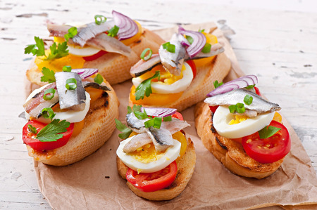 Crostini with anchovies, tomatoes and egg, decorated with greens photo