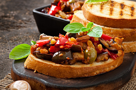 Bruschetta caponata with raisins and pine nuts decorated with a leaf of basil Imagens - 32055927
