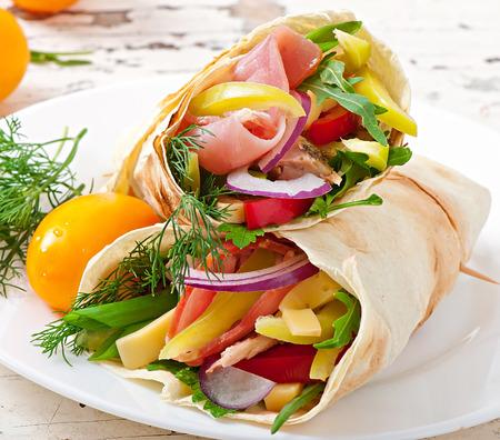 comida sana: Tortilla fresca envuelve con carne y verduras en el plato Foto de archivo