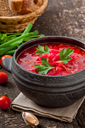 Traditional Ukrainian Russian vegetable borsch on the old wooden background photo