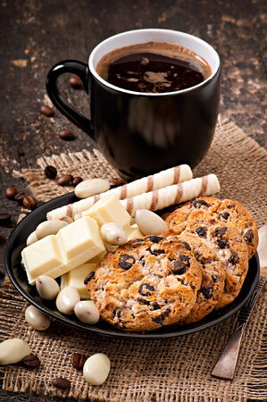Cup of coffee with white chocolate, almonds and cookies photo