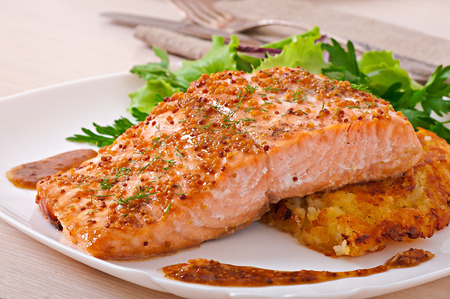 Baked salmon with honey-mustard sauce and potato gratin Stock Photo
