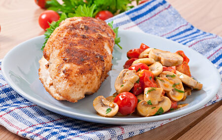Chicken fillet in crispy breadcrumbs garnished with mushrooms and tomatoes photo