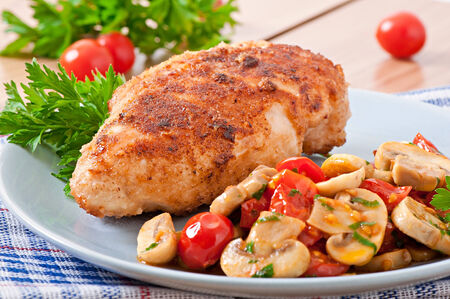 breadcrumbs: Chicken fillet in crispy breadcrumbs garnished with mushrooms and tomatoes Stock Photo