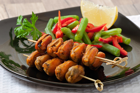 bens: Fried mussels with onions on skewers c garnish of green beans and paprika