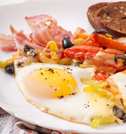 Breakfast - fried eggs with bacon, tomatoes, olives and slices of cheese photo