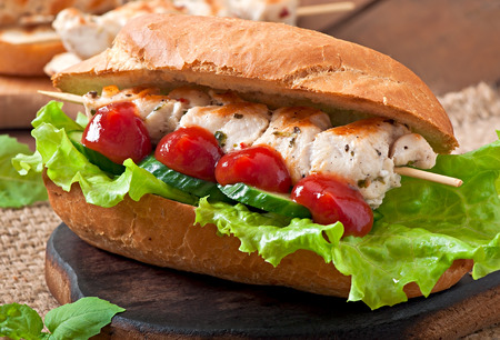 chicken sandwich: Big sandwich with chicken kebab and lettuce