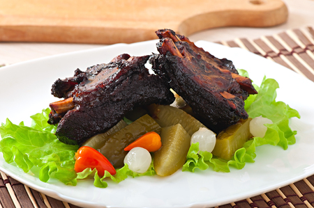 Baked beef ribs in honey soy marinade with pickled vegetables photo