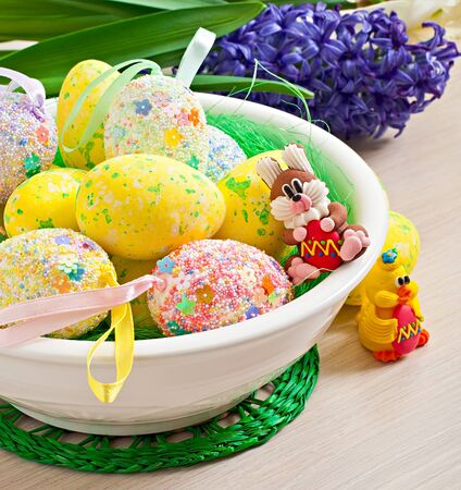 Easter eggs and flowers on wooden background photo