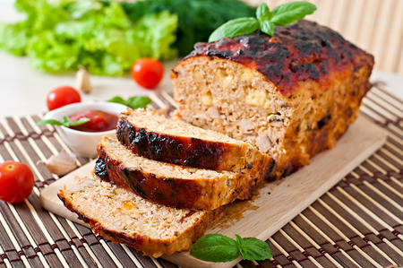 meatloaf: Homemade ground meatloaf with ketchup and basil Stock Photo