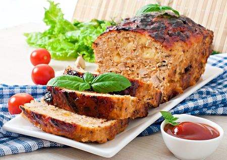 Homemade ground meatloaf with ketchup and basil photo