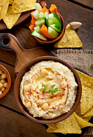 comida arabe: Hummus casera saludable con verduras, aceite de oliva y chips de pita Foto de archivo