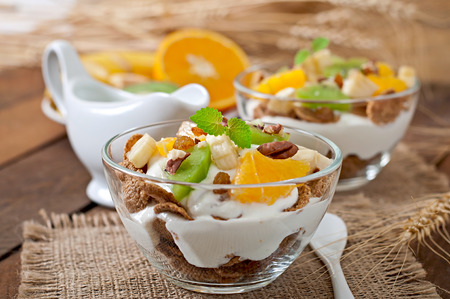 dessert: Healthy dessert with muesli and fruit in a glass bowl on the table