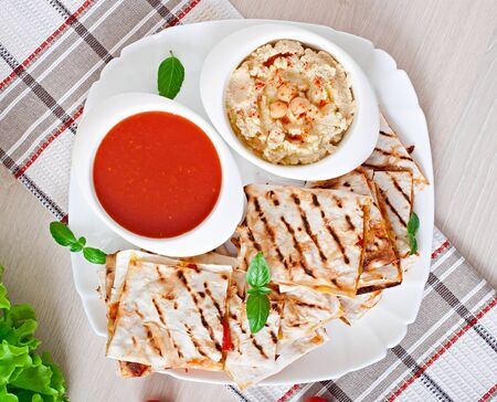 prepared food: Mexican Quesadilla sliced with vegetables and sauces on the table. Stock Photo