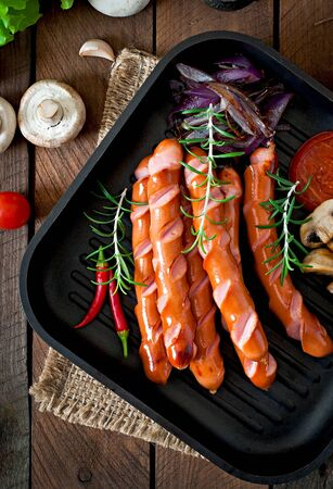 Grilled sausages with vegetables on a frying pan photo