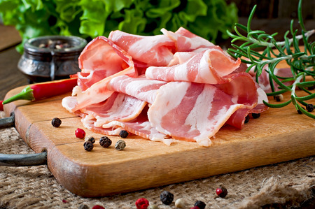 Slices of bacon on the wooden background Stock Photo