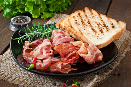 Fried bacon and toast on a black plate on a wooden background photo