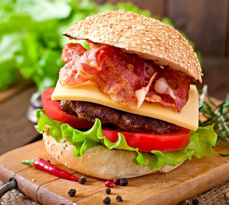 bacon: Big sandwich - hamburger burger with beef, cheese, tomato and fried bacon