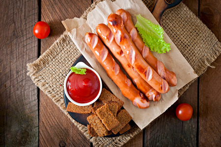 frankfurters: Grilled sausages, crackers and beer on a wooden background in rustic style Stock Photo
