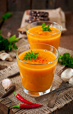 woodenrn: Delicious cream of pumpkin soup in a glass on wooden table