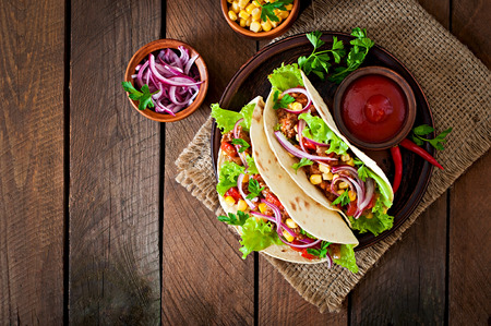 Mexican tacos with meat, vegetables and red onion Stock Photo