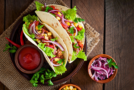 snack food: Mexican tacos with meat, vegetables and red onion Stock Photo