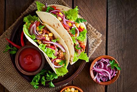 tortilla de maiz: Tacos mexicanos con carne, verduras y cebolla roja