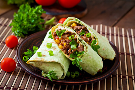meal: Burritos wraps with minced beef and vegetables on a wooden background