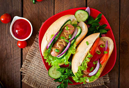 hotdog sandwiches: Hotdog with ketchup, mustard, lettuce and vegetables on wooden table