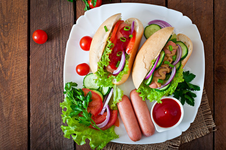 hotdog: Hotdog with ketchup, mustard, lettuce and vegetables on wooden table