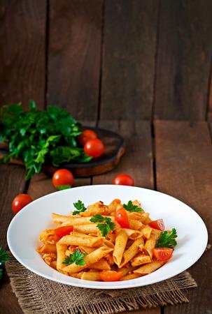 Penne-Nudeln in Tomatensauce mit Huhn, Tomaten auf einem hölzernen Hintergrund