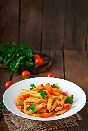 and tasty: Penne pasta in tomato sauce with chicken, tomatoes on a wooden background