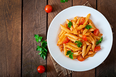 meat dish: Penne pasta in tomato sauce with chicken, tomatoes on a wooden background