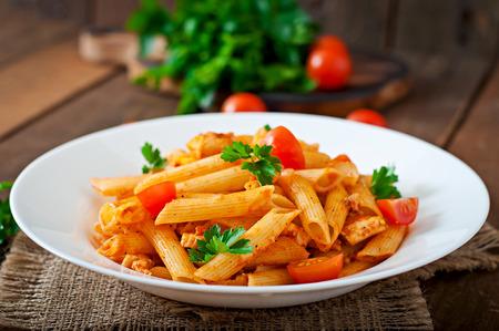 tomates: Penne � la sauce tomate avec du poulet, les tomates sur un fond de bois Banque d'images
