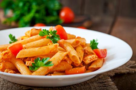 italienisches essen: Penne-Nudeln in Tomatensauce mit Huhn, Tomaten auf einem hölzernen Hintergrund