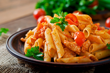 Penne pasta in tomato sauce with chicken, tomatoes on a wooden background